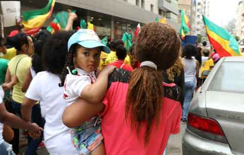An Ethiopian migrant domestic worker holds a child during the annual Migrant Workers' March, held in Beirut every year on Workers' Day to advocate for better working conditions and accountability for migrant abuse and deaths. Credit: Anti-Racism Movement]