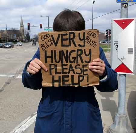 Caption: Homeless person begging on Lake Cook Road in Buffalo Grove Illinois. The photographer talked to the young man and his homelessness was the result of a a loss of a job and the loss of his roommate. Credit: Hajee