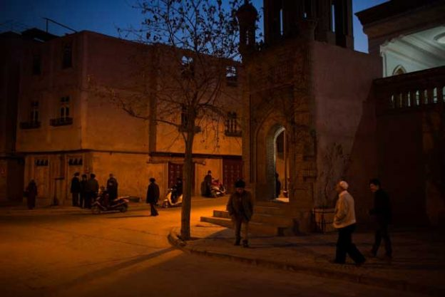 Men congregating outside a mosque after evening prayer in the old city in Kashgar, Xinjiang, China.