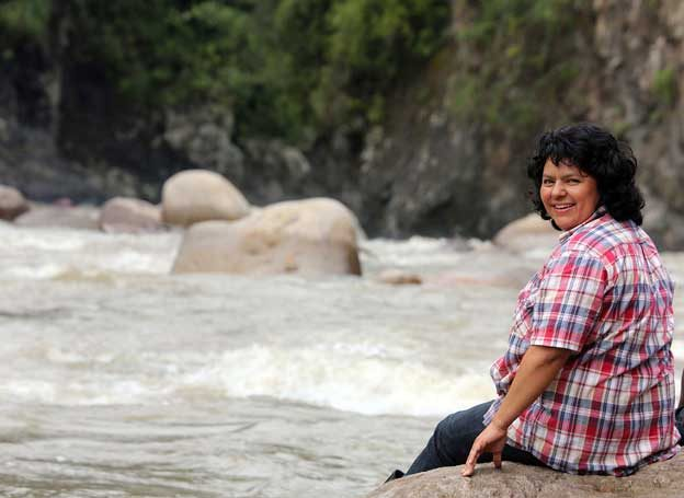 Photo: Beata Cáceres in 2016 sitting next to the Gualcarque river, which she defended against construction of a mega-dam project, a defense which resulted in her murder. Credit © Goldman Environmental Prize
