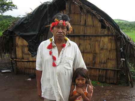 Photo: Hamilton Lopes and his daughter, members of the Guarani indigenous community, stand in front of their hut. Credit: Mario Osava/IPS